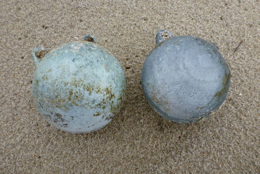 Two small grayish and bluish lugged floats on sand