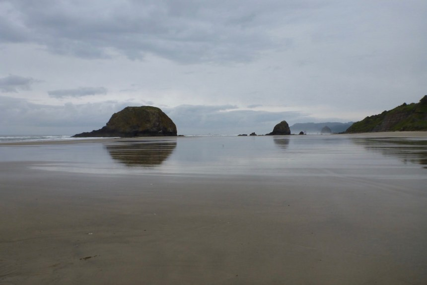 A sandy foreground, cloudy skies, and sea stacks in the distance