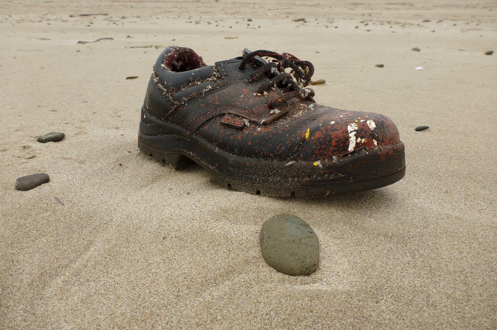Right lace up shoe spattered with paint on sand