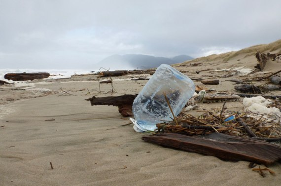 Plastic drinking water storage jug tossed up on the sand by the last high tide