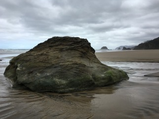 large rock jutting out of the sand with sea stacks in the background