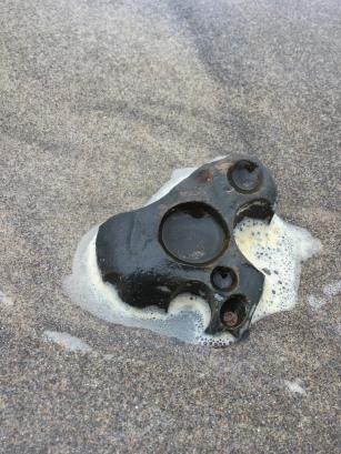rock with holes on beach sand