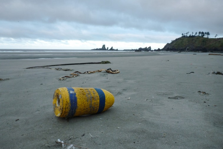 Lost crab buoy on sand at low tide, cloudy skies