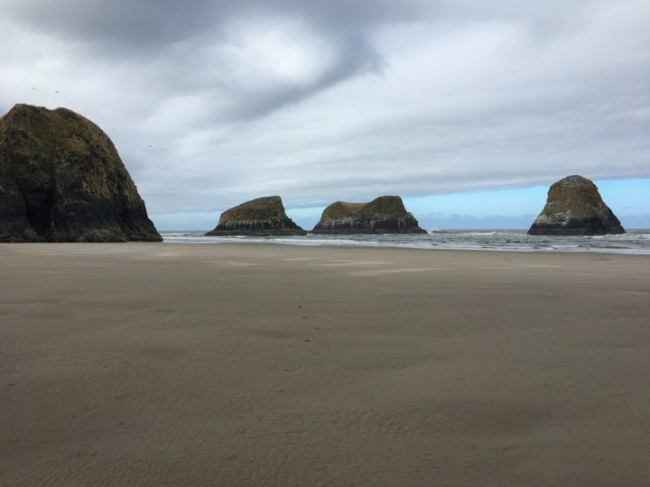 Four sea stacks, cloudy skies, and beach sand in the foreground