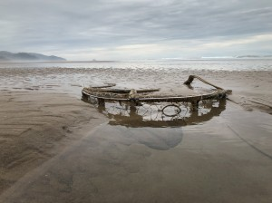 Dungeness crab trap half buried in sand, exposed at low tie