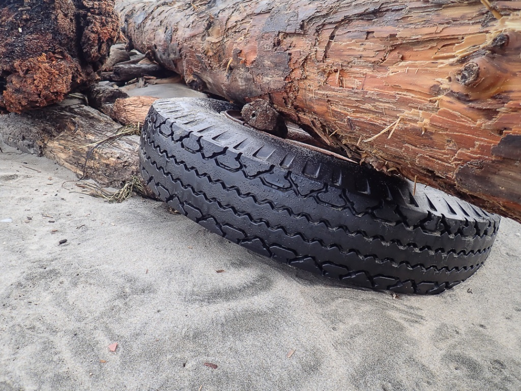 Tire trapped under a large drift log