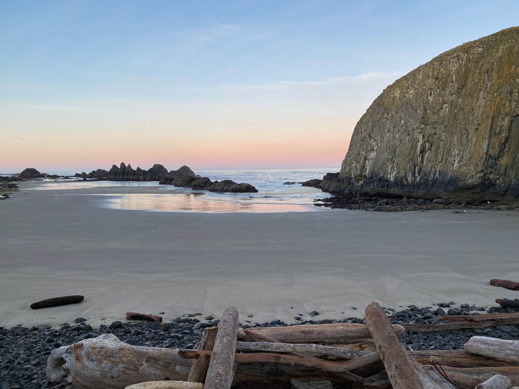Looking over the big wood wrack across the beach and out to see; plenty of rocks at the surf line; a ; little dawn color at the horizon, otherwise a clear blue sky.
