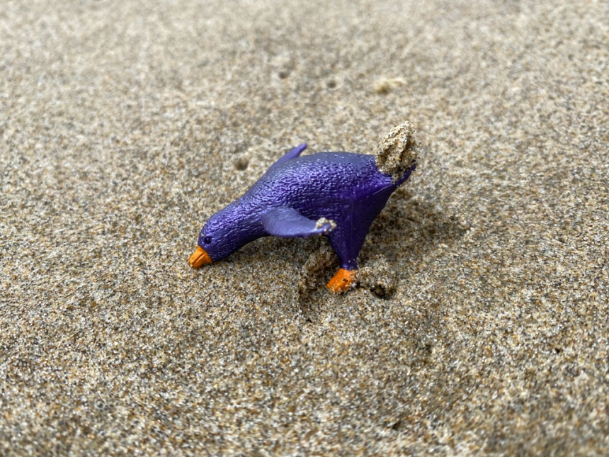 A small royal indigo-colored penguin-like plastic toy